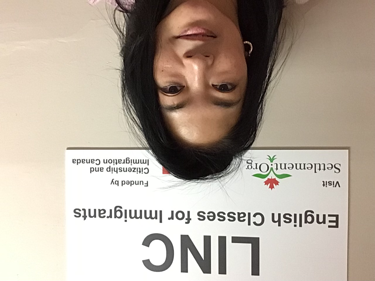 A woman (Emmalyn) standing in front of a sign reading LINC English Classes for Immigrants