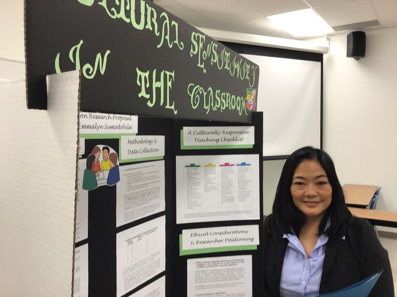 A woman (Emmalyn) smiling and standing next to a presentation board